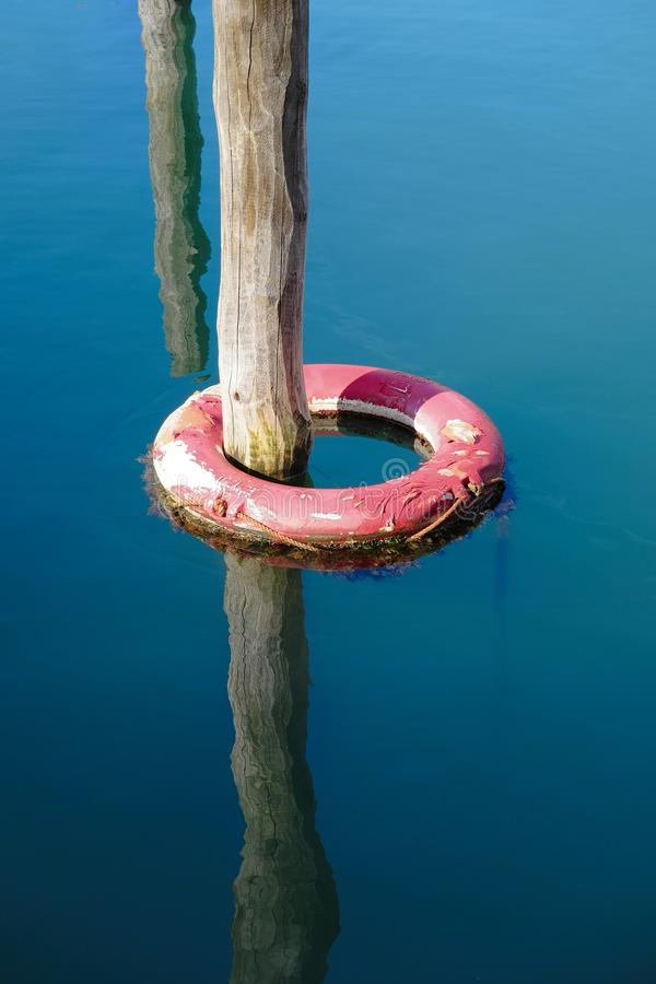 Lifebelt. Life buoy in water anchored to the dock royalty free stock photo