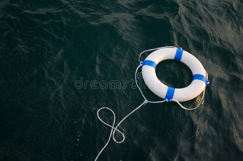 Lifebelt, lifebuoy in a dangerous sea for help, safety,security. Lifebelt, lifebuoy in a dangerous dark sea for help, safety,security stock photos