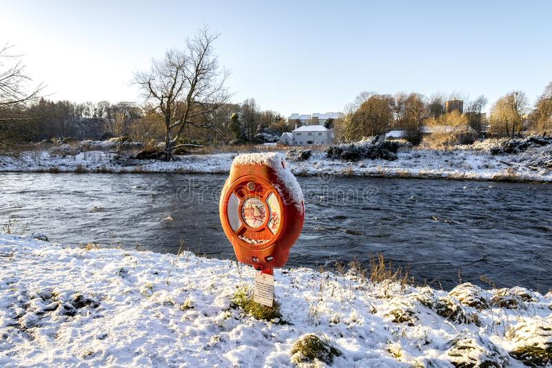 A lifebelt post covered by snow on the shores of Don river flowing through Seaton Park, Aberdeen, Scotland. December 2017 stock photo