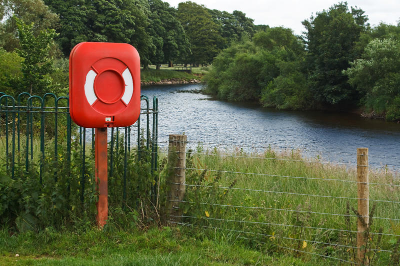 Lifebelt riverside. Red lifebelt beside a river in the country, used as a floatation device for saving anyone who accidentally falls in the water to stop them royalty free stock images