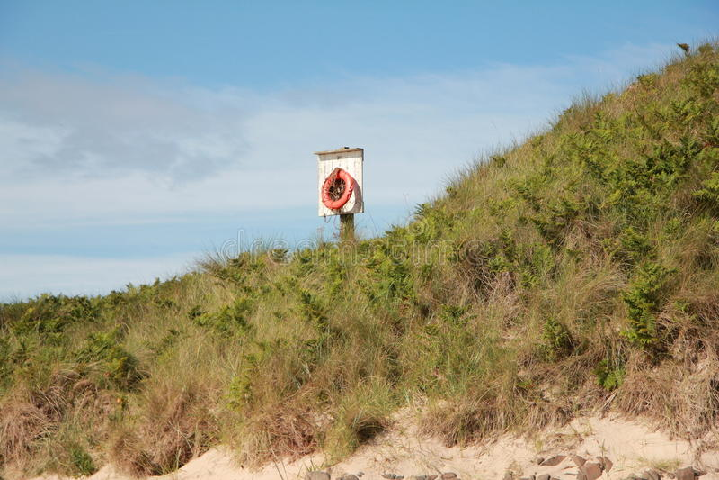 Lifebelt on sand dune 1. Solitary lifebelt on embleton beach sand dune stock photos