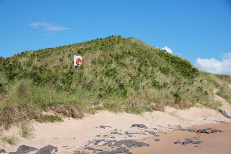 Lifebelt on sand dune 2. Solitary lifebelt on embleton beach sand dune royalty free stock photography
