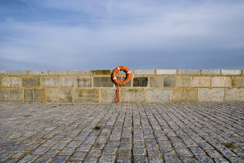 Lifebelt at stonewall near the ocean. Orange lifebelt at stonewall near the ocean royalty free stock images