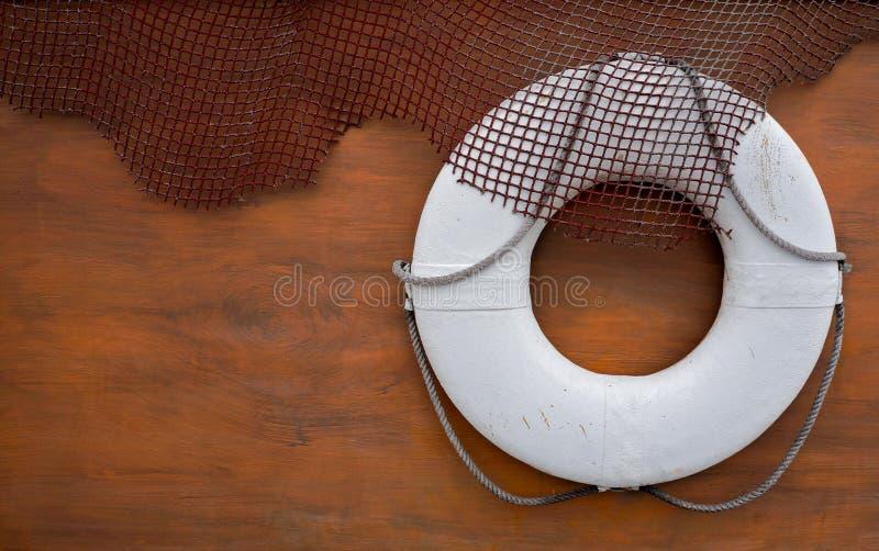 Lifebelt with wood background. White lifebelt and fishing net with wood background stock image