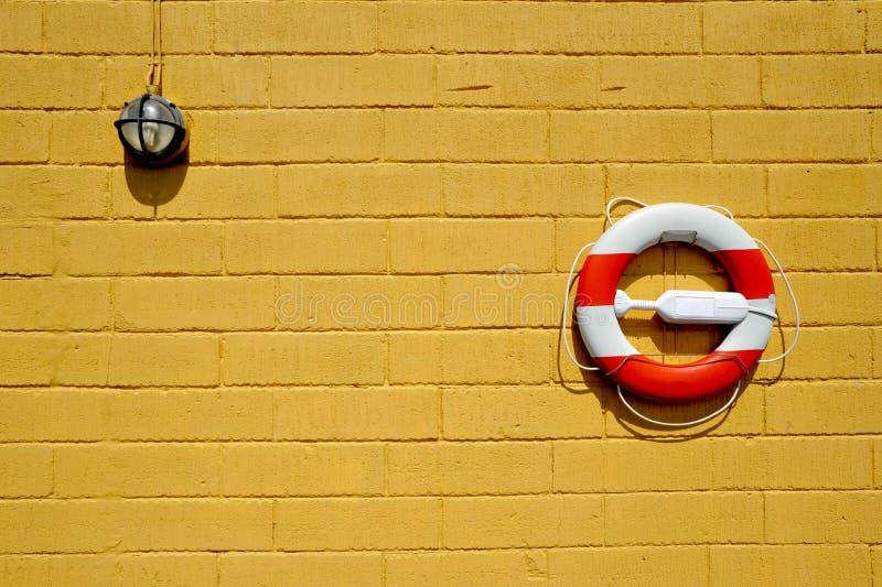 Lifebelt on yellow wall. And light bracket royalty free stock photo