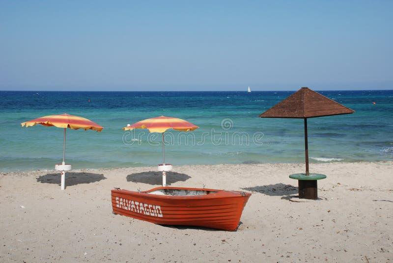 Lifeboat i Trzy Plażowego parasola obraz stock