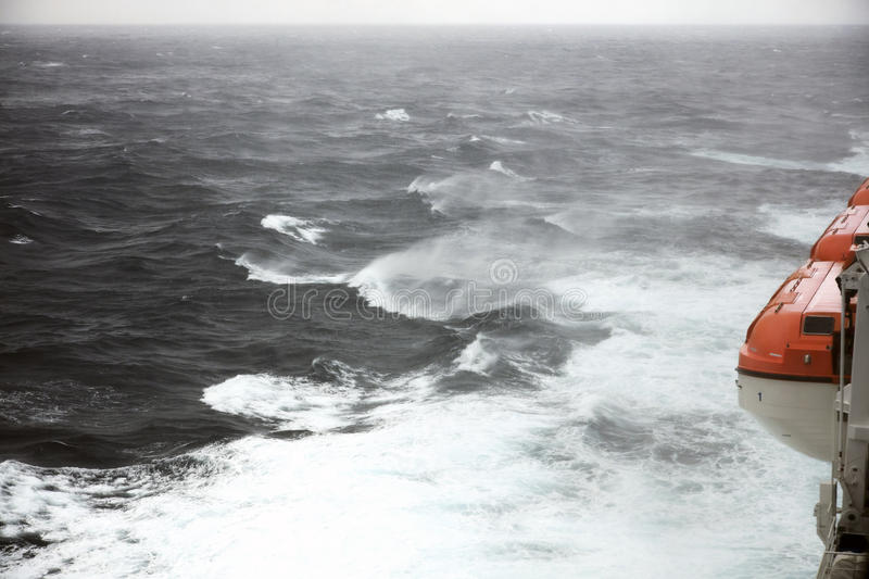 Lifeboats and rough seas. Lifeboats mean a good insurance to passengers on a ship in very rough seas in mid ocean stock image