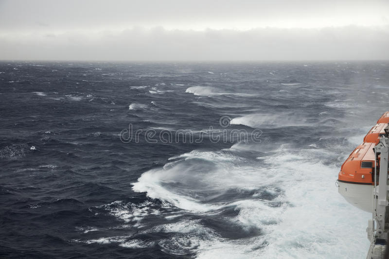 Lifeboats and rough seas. Lifeboats stowed on a ship in very rough seas royalty free stock photos