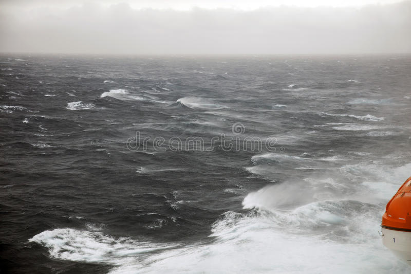 Lifeboats and rough seas. Lifeboats stowed on a ship in very rough seas royalty free stock photo