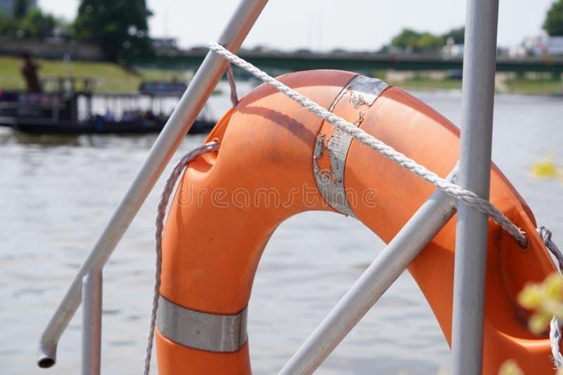 Lifebuoy橙色垂悬在小船一边,安全 划船或划船在河大家的 免版税图库摄影
