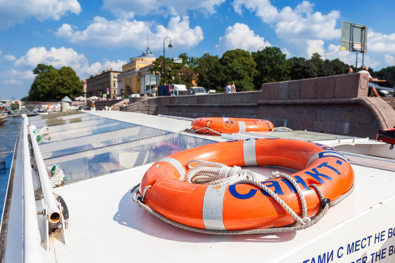 Lifebuoy on the excursion boat in summer sunny day. SAINT PETERSBURG, RUSSIA - AUGUST 7, 2014: Lifebuoy on the excursion boat in summer sunny day stock photo