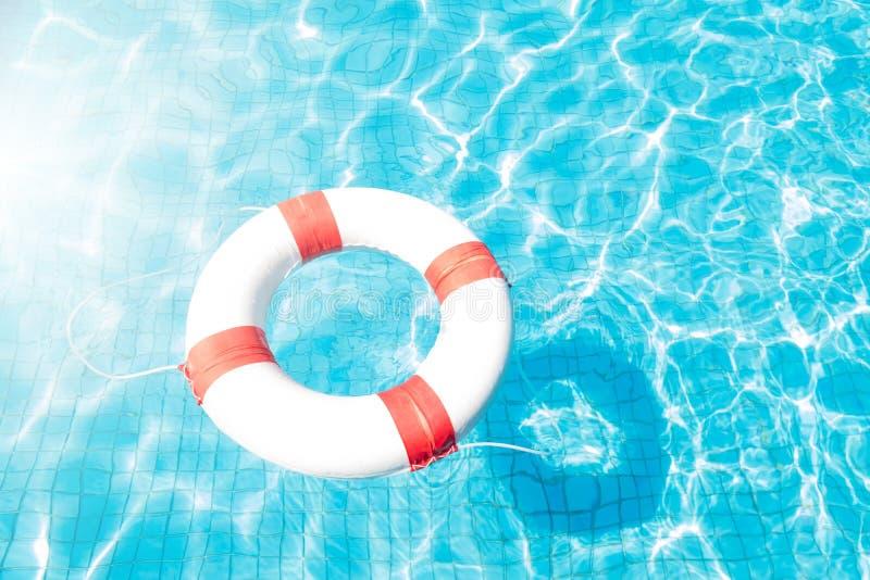 Lifebuoy floating on blue swimming pool. stock photography