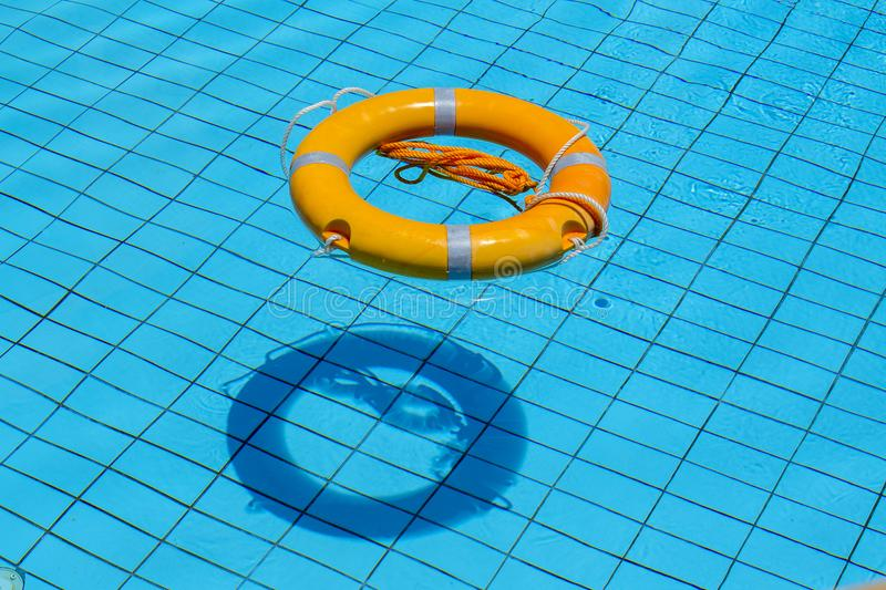 Lifebuoy floating on top of sunny blue water in swimming pool royalty free stock photography