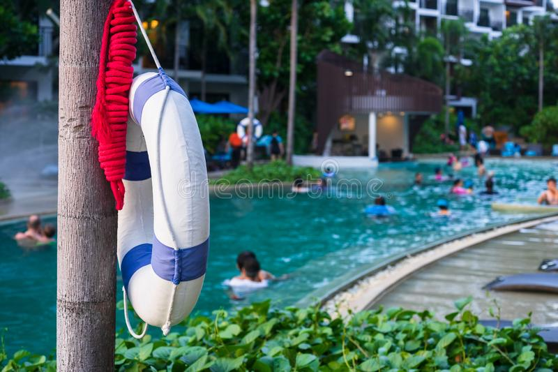 Lifebuoy hanging on a tree next to the outdoor swimming pool for the safety of people with blurred people swimming on a swimming royalty free stock photo