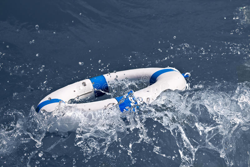 Lifebuoy, lifebelt, life saver in a storm wave as help. Lifebuoy, lifebelt, life saver in a dangerous storm wave as help stock images