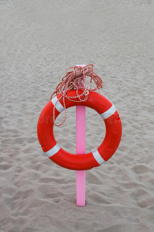 Lifebuoy with a long rope hung on a pink stake royalty free stock photo