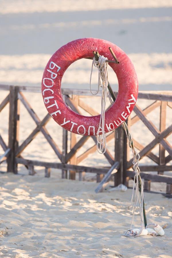 Lifebuoy rzut tonięcie mężczyzna z szyldowym obwieszeniem na ośniedziałym metalu kiju na piaskowatej plaży zdjęcie stock