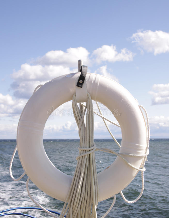 LifeBuoy and Sky. A white lifebuoy vertically framed in front of the ocean. Blue sky, sunlight and few white clouds. Bright light and shades of blue stock image