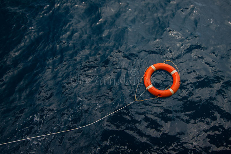 Lifebuoy in a stormy blue sea, Lifebuoy in blue sea, safety equipment in offshore or marine stock photography