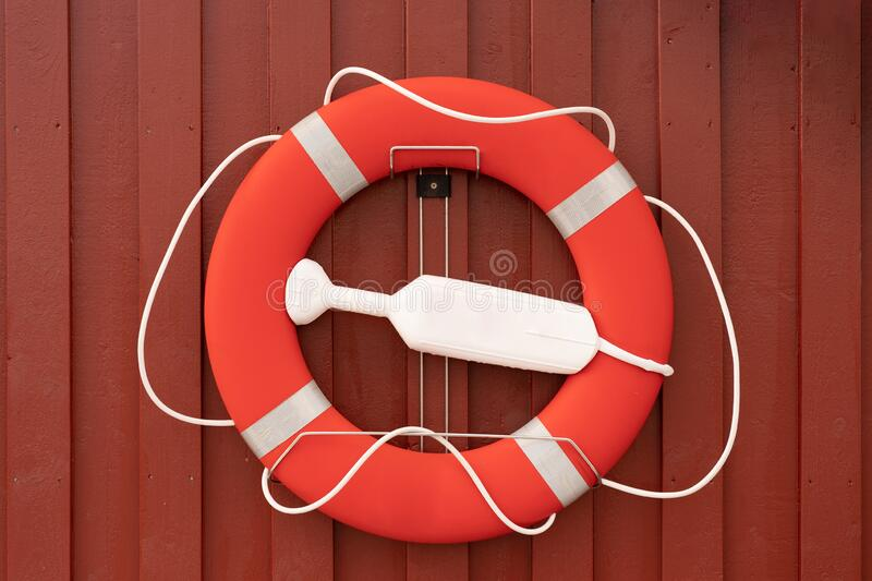 Lifebuoy on traditional red wooden houses stock image