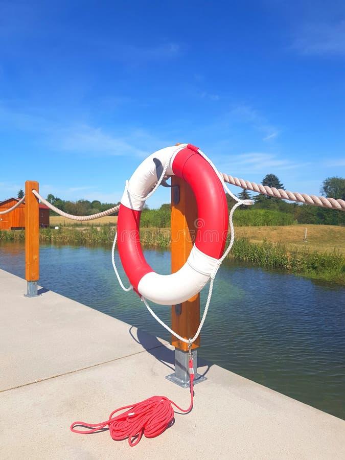 Lifebuoy w czerwonym i białym kolorze na drewnianym legarze zdjęcie royalty free