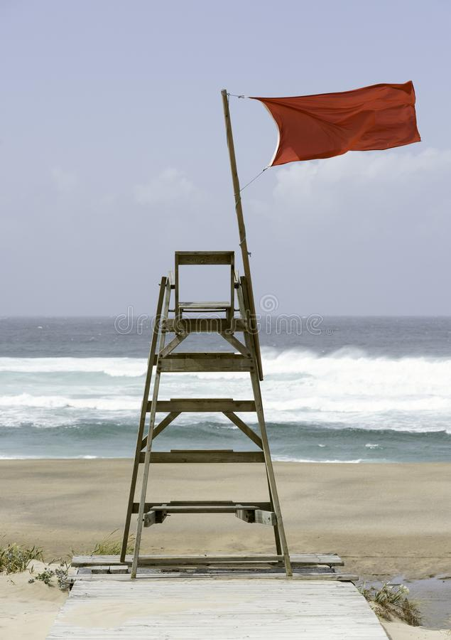 Lifeguard chair with a red flag stock image