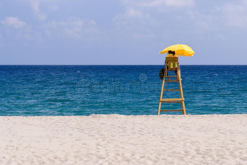Lifeguard, lonely beach, sunny weather. High quality photo of a lifeguard's sitting on a small wooden ladder under bright yellow umbrella and watching for royalty free stock images