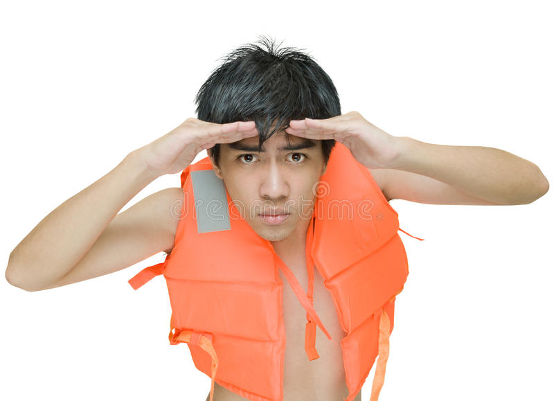 Lifeguard on the lookout. Teenage Asian lifeguard with red life or swimming jacket on the lookout, peering and watching intensely in the distance with his hands royalty free stock photography