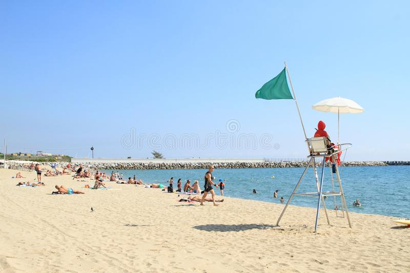 Lifeguard on post on beach in Barcelona. Lifeguard on post with seat, white umbrella for shade and green flag blowing in the wind announcing that swimming in sea royalty free stock photography