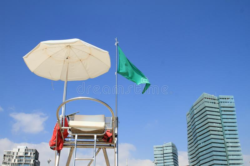 Lifeguard post on beach in Barcelona. Lifeguard post with seat, white umbrella for shade and green flag blowing in the wind announcing that swimming in sea is royalty free stock images