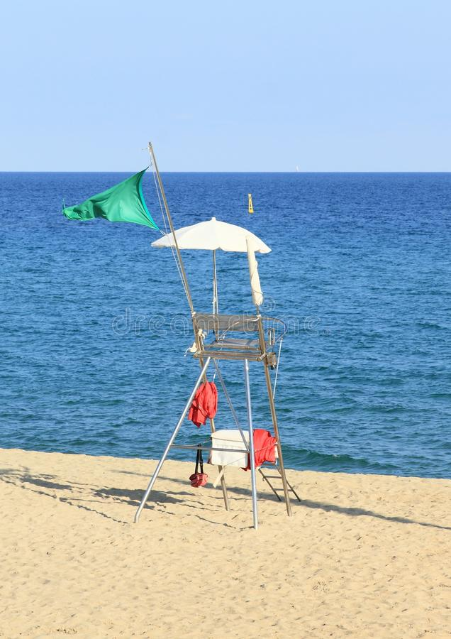 Lifeguard post on beach in Barcelona. Lifeguard post with seat, white umbrella for shade and green flag blowing in the wind announcing that swimming in sea is stock photo