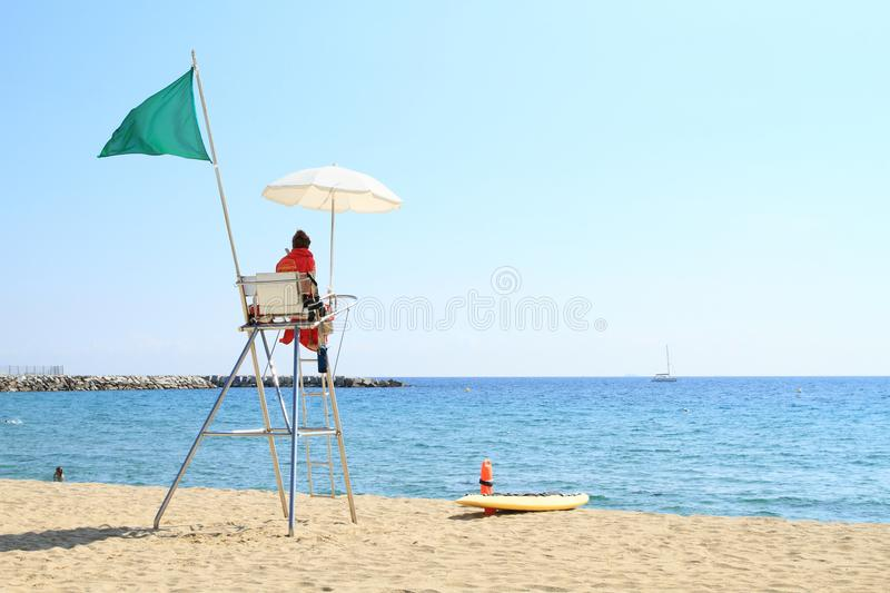 Lifeguard on post on beach in Barcelona. Lifeguard on post with seat, white umbrella for shade and green flag blowing in the wind announcing that swimming in sea stock photography