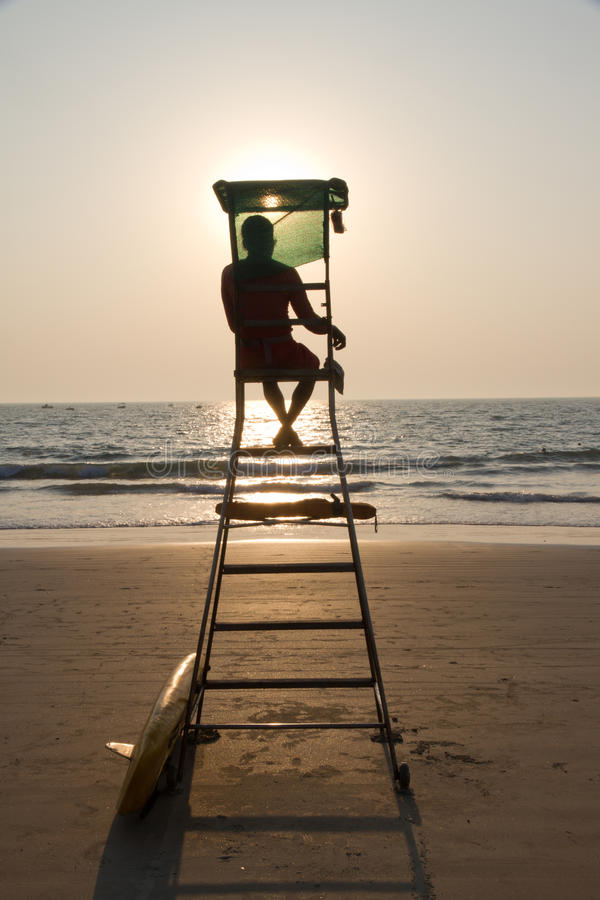 Lifeguard silhouette overlooking tropical beach stock image