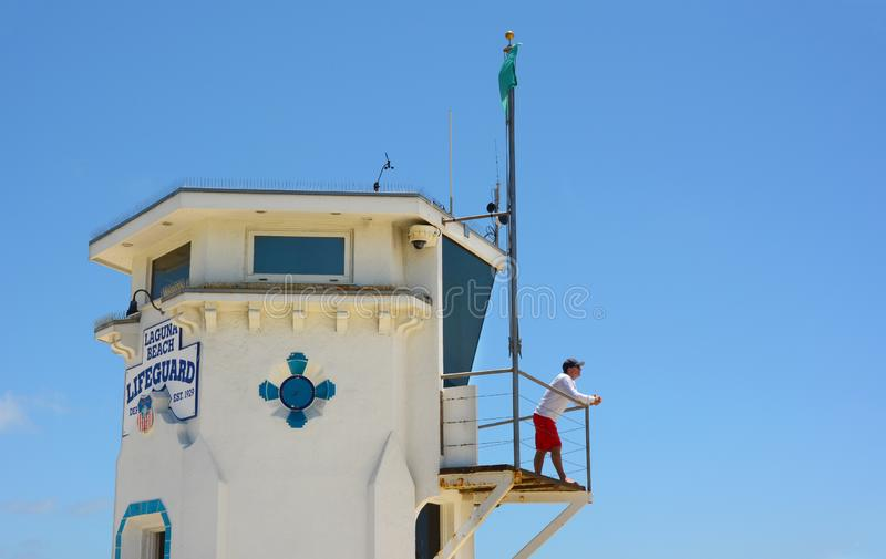 A lifeguard stands watch on the Main Beach Tower in the popular Southern California beach town. LAGUNA BEACH, CALIFORNIA - MAY 28, 2019: A lifeguard stands watch stock image