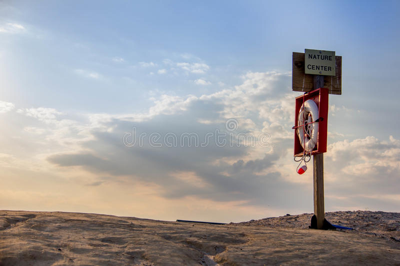 Lifeguard Station on Assateague Island. A signpost with Nature Center written over it, with a lifesaver stocked away. Behind is a beautiful sunset and a bit of stock images