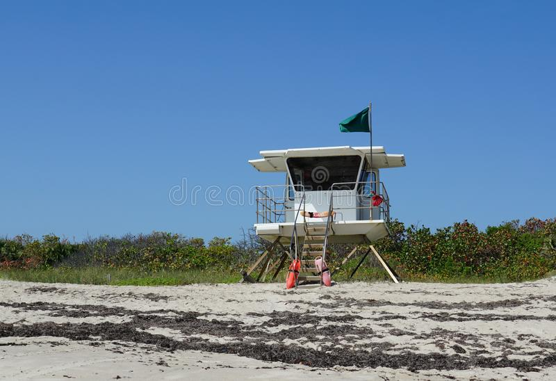 Lifeguard station on Pepper Park beach in Ft. Pierce, Florida on Hutchinson Island. Flying a green flag signaling it is all clear to swim on a warm sunny day stock photos