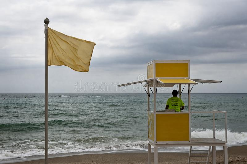 Lifeguard on a lifeguard tower watching on a beach with yellow caution flag royalty free stock photos