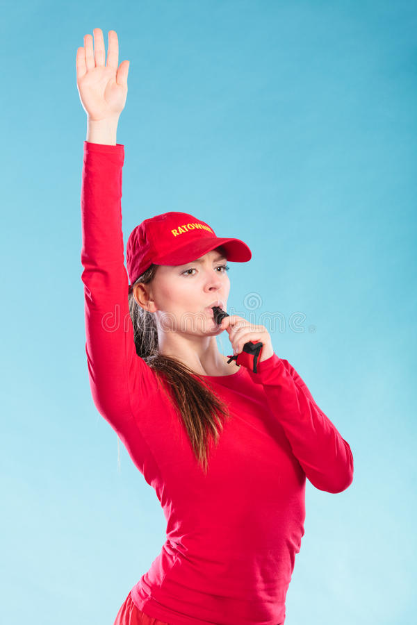 Lifeguard woman in cap on duty blowing whistle. stock images