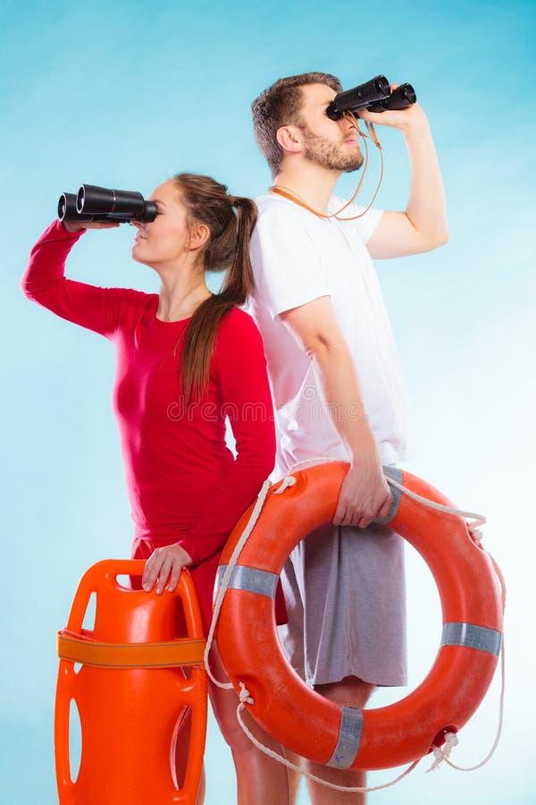 Lifeguards στο καθήκον που κοιτάζει μέσω των διοπτρών στοκ φωτογραφίες