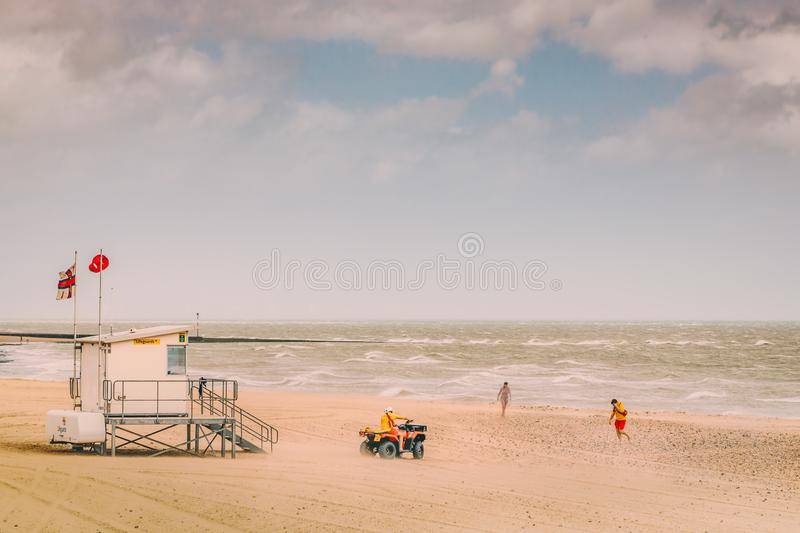 Lifeguards on Ramsgate main sands beach monitor a lady swimmer during high winds and sand blowing in royalty free stock images