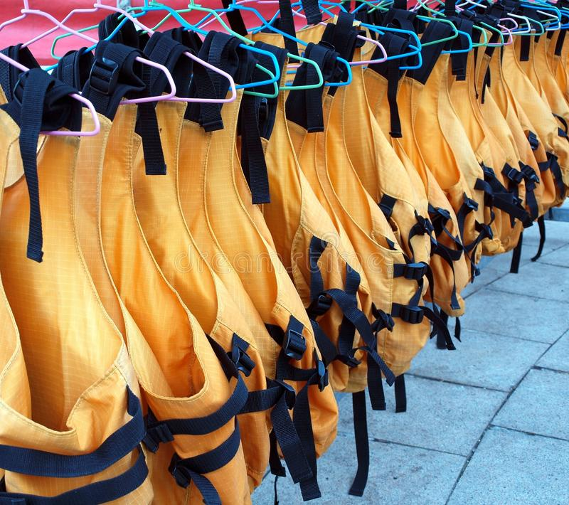 Lifejackets on Hangers. Orange life vests are drying on clothes hangers stock photo