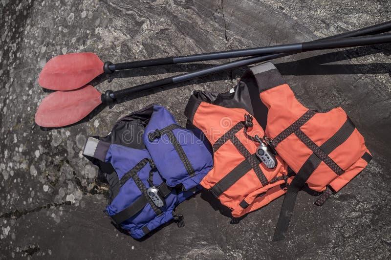 Lifejackets and radio are on the rocky coast, near lie oars. Two life jackets and a radio are on the rocky coast, near lie oars royalty free stock photo
