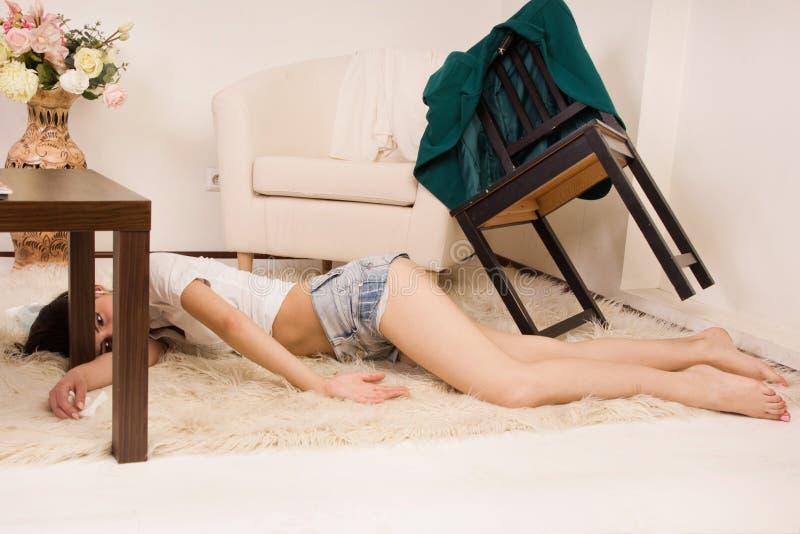 Lifeless woman lying on the floor (imitation) stock images