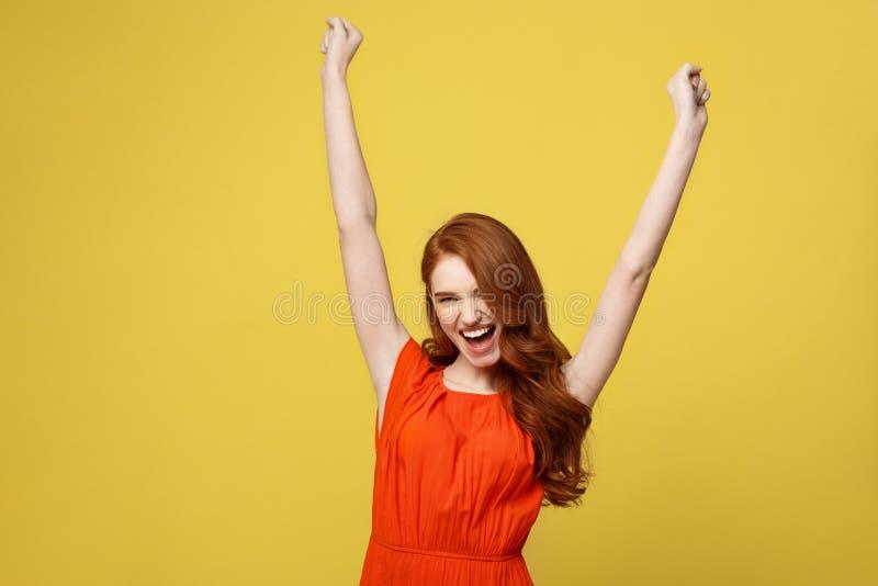 Lifestlye、自由和幸福概念-显示手的橙色华美的礼服的画象年轻美丽的愉快的女孩  免版税库存图片