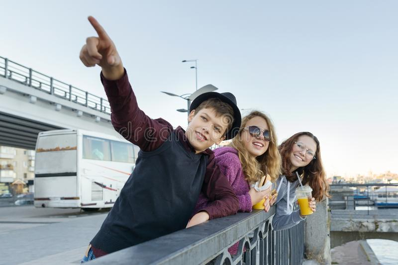 Lifestyle of adolescents, boy and two teen girls are walking in the city. Laughing, talking children eating street food, having royalty free stock photography