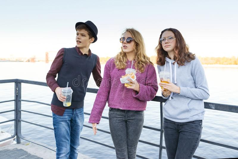 Lifestyle of adolescents, boy and two teen girls are walking in the city. Laughing, talking children eating street food, having stock images