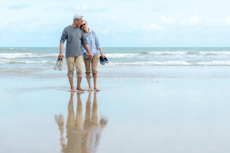 Lifestyle asian senior couple happy walking hug and relax on the beach.  Tourism elderly family travel leisure and activity after royalty free stock photography