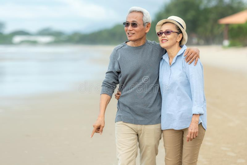 Lifestyle asian senior couple happy walking and relax on the beach.  Tourism elderly family travel leisure and activity after reti. Rement in vacations and stock photo