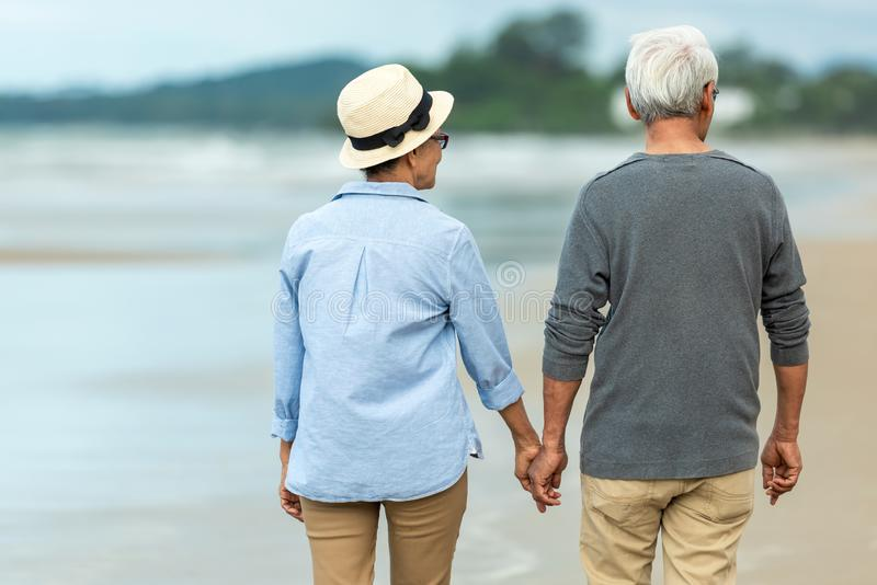 Lifestyle asian senior couple happy walking and relax on the beach.  Tourism elderly family travel leisure. And activity after retirement in vacations and stock photography