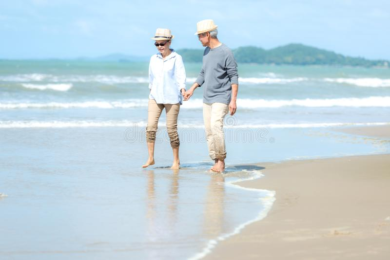 Lifestyle asian senior couple walking happy and relax on the beach. stock photo